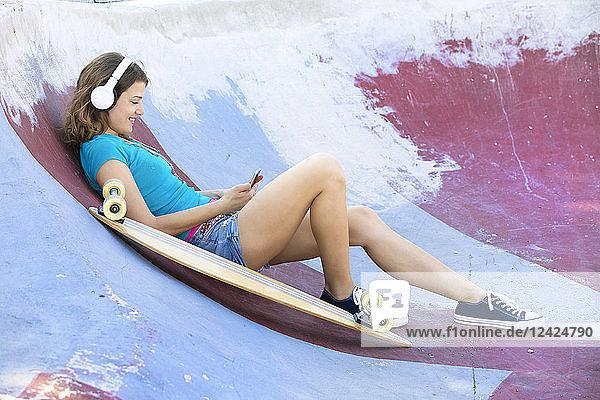 Female longboarder with earphones lying in halfpipe