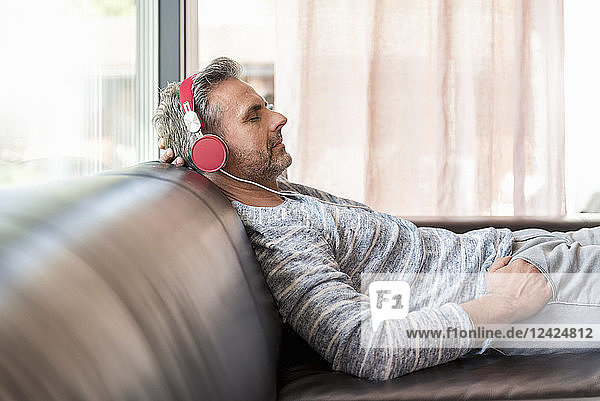 Relaxed mature man lying on couch at home wearing headphones