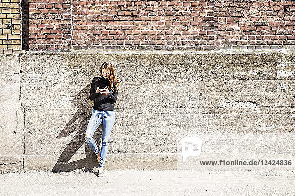 Woman with leaning against wall using cell phone