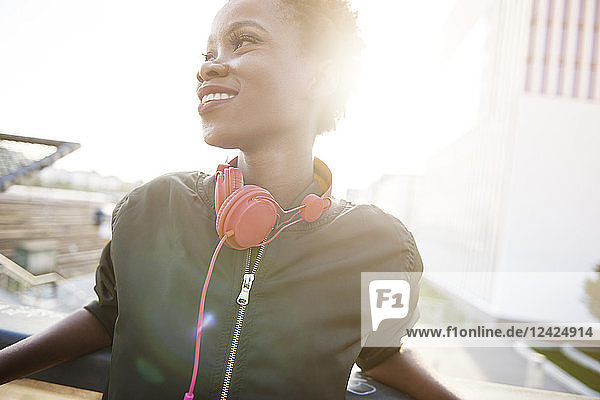 Smiling young woman with headphones at backlight Smiling young woman with headphones at backlight