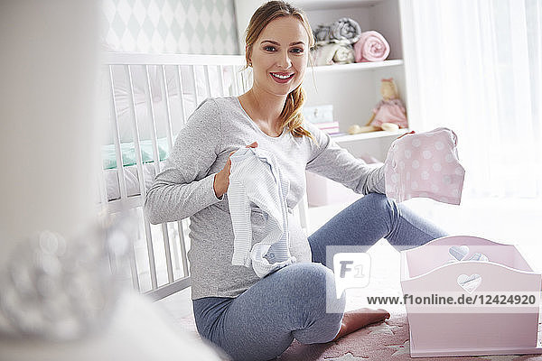 Pregnant woman with baby clothes in baby room