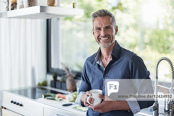 Portait of smiling mature man at home in kitchen with cup of coffee