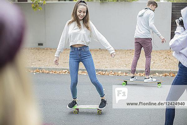Happy teenage friends riding skateboard on the street