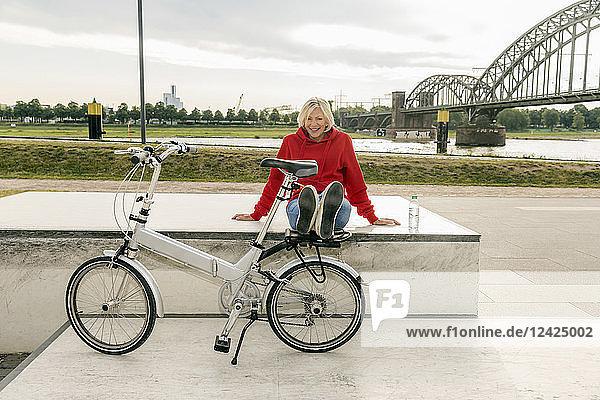 Smiling senior woman with city bike having a break