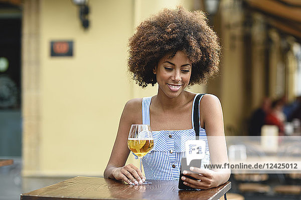 Portrait of young woman with smartphone drinking beer outdoors