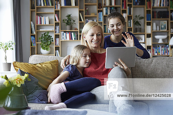 Mother and her daughters sitting on couch  having fun using digital laptop