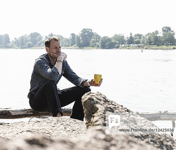 Mature man sitting at Rhine riverbank  looking at distance