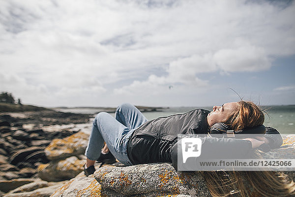 France  Brittany  Landeda  young woman wearing headphones lying at the coast
