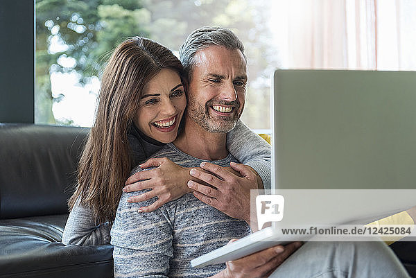 Happy couple on couch at home sharing a laptop