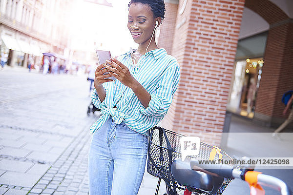 Portrait of smiling woman with earphones and cell phone in the city Portrait of smiling woman with earphones and cell phone in the city