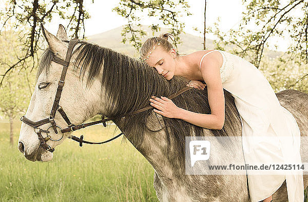 Beautiful young woman riding horse  wearing white summer dress