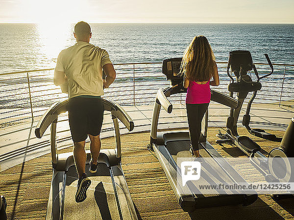 Man and woman exercising on patio over sea