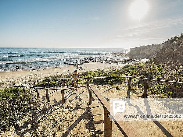 USA  California  Newport Beach  Woman running up stairs