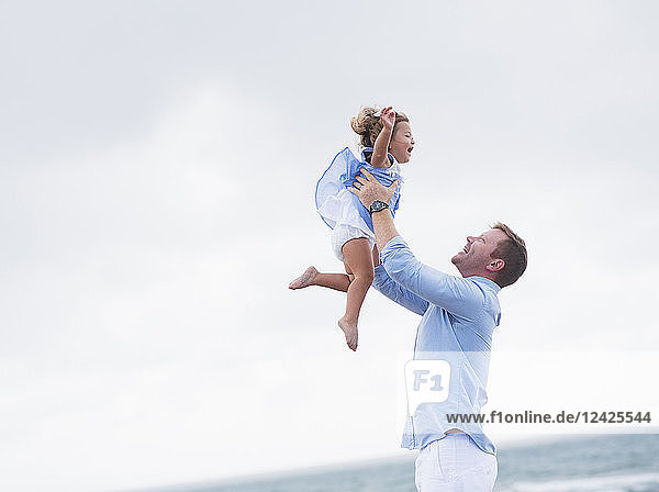 Father lifting daughter