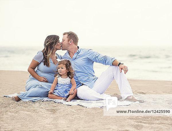 Family sitting on blanket on beach