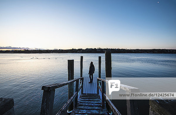 Man standing on pier at dawn
