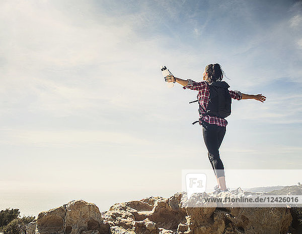 Woman on hike with arms outstretched