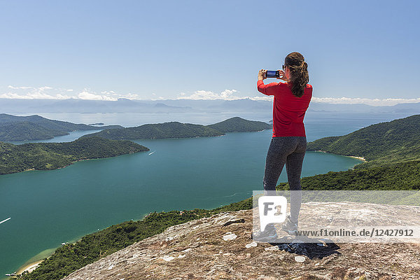 Rear view shot of single woman photographing view of sea from mountain with smartphone  Saco do Mamangua  Paraty  Costa Verde  Brazil