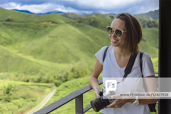 Waist up shot of smiling female tourist with sunglasses and camera at tea plantation  Cameron Highlands  Malaysia