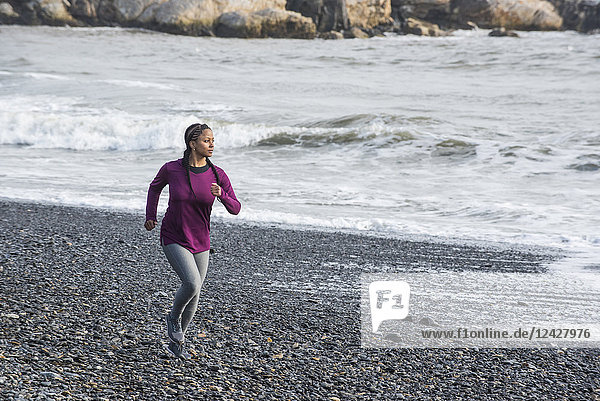 Front view of single woman running on rocky beach  Kittery  Maine  USA