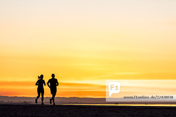 Rear view silhouettes of man and woman running at sunrise