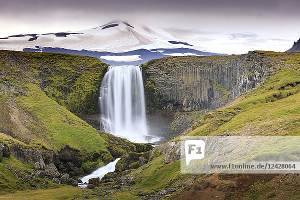 Majestic natural scenery with view of Svodufoss waterfall and Snaefellsjokull volcano  Iceland