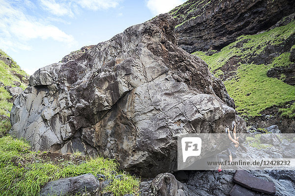 Distant view of adventurous woman climbing boulder  Maui  Hawaii Islands  USA