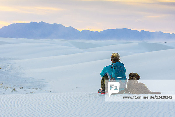 Rear view of woman and dog sitting while hiking in White Sands National Monument  Alamogordo  New Mexico  USA