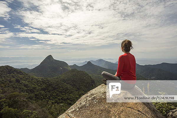 Rear view of single woman sitting on rock in scenery with mountains  Tijuca Forest National Park  Rio de Janeiro  Brazil