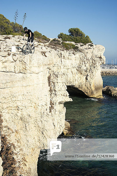 Distant view shot of adventurous mountain biker on coastal cliffs