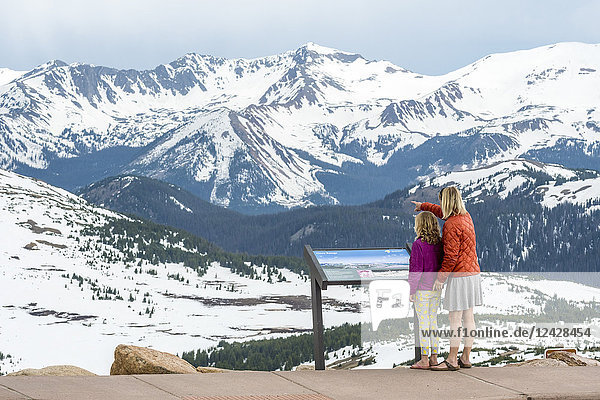 Mother and daughter standing in beautiful natural scenery with snowcapped mountains at Trailridge Road looking at Never Summer Range  Rocky Mountain National Park  Estes Park  Colorado  USA