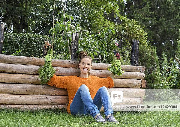 Junge Frau im Garten  erntet Karotten und Radieschen