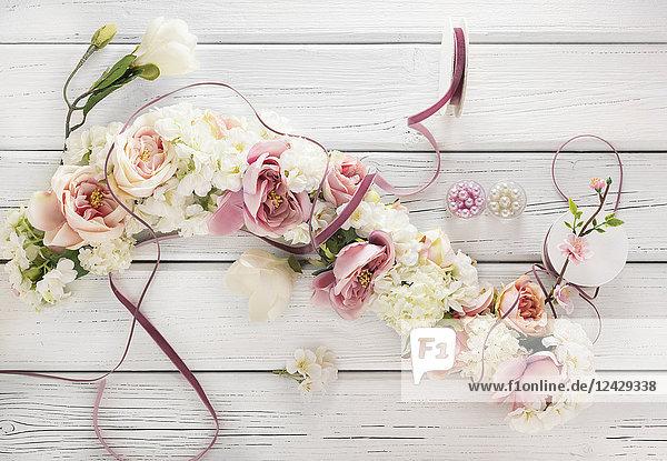 Blumengirlande auf weißem Holztisch