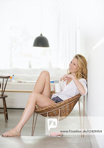 Blonde Frau zuhause  sitzt bequem in Stuhl  mit Kaffeetasse
