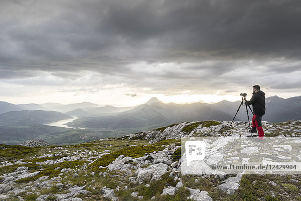 Photographer with camera on tripod in mountains  Palencia  Palencia Province  Spain