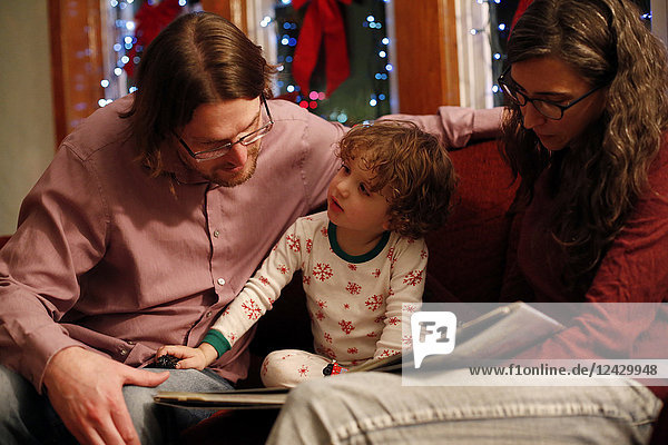 Family of two parents and boy reading together picture book during Christmas