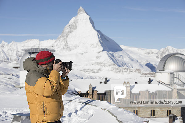 Side view shot of photographer with camera with Matterhorn in background  Zermatt  Valais Canton  Switzerland