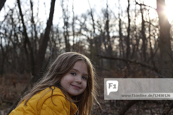 Headshot of smiling girl looking at camera in forest