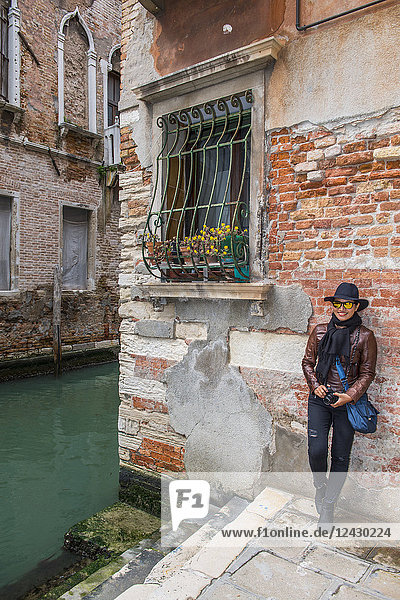 Front view shot of female tourist leaning against wall in Venice  Italy