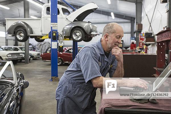 A senior Caucasian male car mechanic working on his laptop computer in his classic car repair shop.