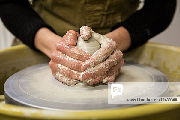 Close up of potter wearing apron working on pottery wheel  shaping clay.