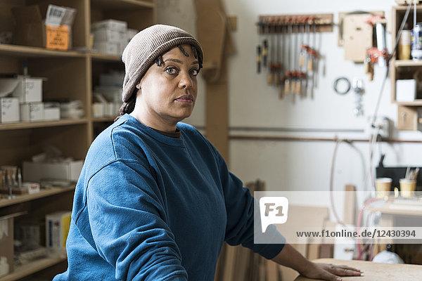 Porträt einer schwarzen Tischlerin in einer großen Holzwerkstatt.