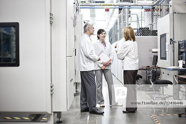 Ein Team von Technikern  die an einem Problem in einem technischen Forschungs- und Entwicklungsstandort arbeiten.