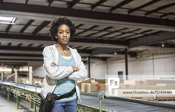 Porträt einer afroamerikanischen Lagerarbeiterin in einem großen Vertriebslager mit in Pappkartons gelagerten Produkten.