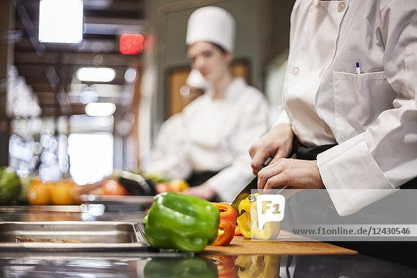 Eine Nahaufnahme der Hände eines Küchenchefs  der in einer Großküche Gemüse schneidet.