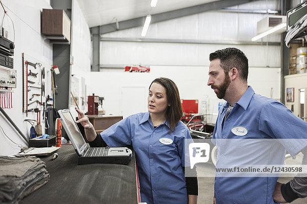 Zwei Mechaniker arbeiten an einem Laptop-Computer in einer Reparaturwerkstatt.