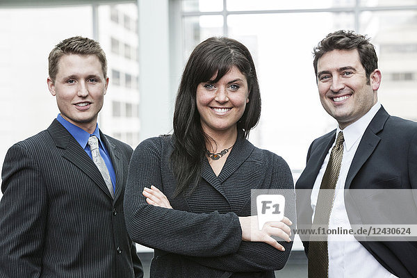 A group portrait of three business people  with a Caucasian woman as the lead.