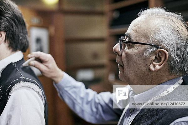 Schneider  der eine Jacke mit Schneiderkreide an einen Kunden anpasst  um den Stoff zu markieren. Schneider, der eine Jacke mit Schneiderkreide an einen Kunden anpasst, um den Stoff zu markieren.
