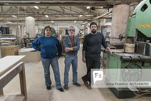 Portrait eines Teams von drei gemischtrassigen Tischlern in einer großen holzverarbeitenden Fabrik.