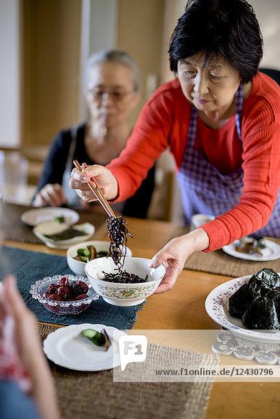 Frau mit Schürze steht am Küchentisch  hält Schüssel  serviert Essen mit Stäbchen.